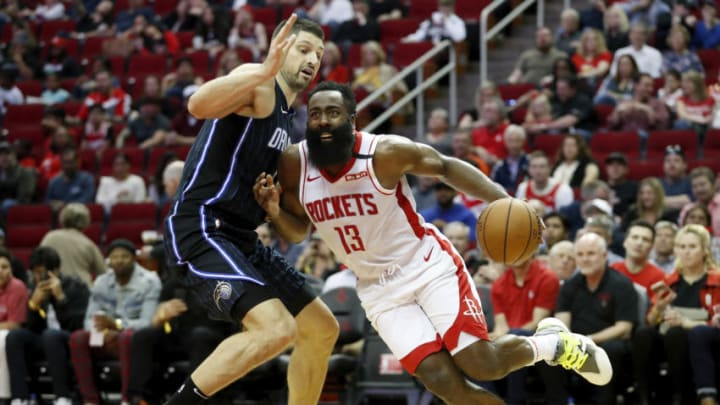 HOUSTON, TEXAS - MARCH 08: James Harden #13 of the Houston Rockets drives to the basket while defended by Nikola Vucevic #9 of the Orlando Magic in the second half at Toyota Center on March 08, 2020 in Houston, Texas. NOTE TO USER: User expressly acknowledges and agrees that, by downloading and or using this photograph, User is consenting to the terms and conditions of the Getty Images License Agreement. (Photo by Tim Warner/Getty Images)