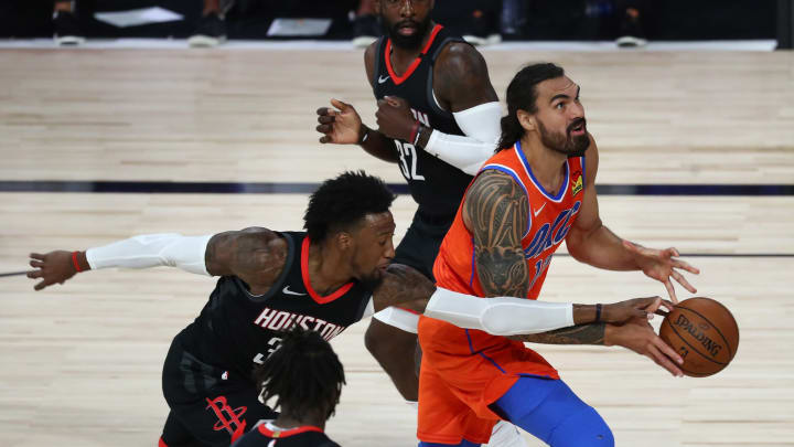 Steven Adams #12 of the Oklahoma City Thunder drives against Robert Covington #33 of the Houston Rockets (Photo by Kim Klement – Pool/Getty Images)