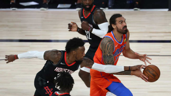 Steven Adams #12 of the Oklahoma City Thunder drives against Robert Covington #33 of the Houston Rockets (Photo by Kim Klement - Pool/Getty Images)