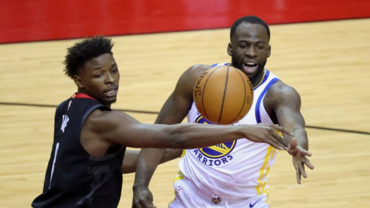 HOUSTON, TEXAS - MARCH 17: Draymond Green #23 of the Golden State Warriors dishes a pass over Jae'Sean Tate #8 of the Houston Rockets during the first quarter of a game at the Toyota Center on March 17, 2021 in Houston, Texas. NOTE TO USER: User expressly acknowledges and agrees that, by downloading and or using this photograph, User is consenting to the terms and conditions of the Getty Images License Agreement. (Photo by Carmen Mandato/Getty Images)