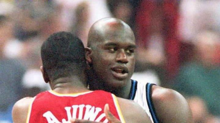 Orlando Magic center Shaquille O'Neal (R) hugs Houston Rockets center Hakeem Olajuwon (Photo credit should read CALVIN KNIGHT/AFP via Getty Images)