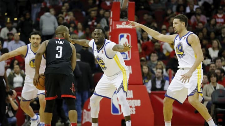 HOUSTON, TX - JANUARY 04: Chris Paul #3 of the Houston Rockets controls the ball defended by Klay Thompson #11 of the Golden State Warriors and Draymond Green #23 in the second half at Toyota Center on January 4, 2018 in Houston, Texas. NOTE TO USER: User expressly acknowledges and agrees that, by downloading and or using this Photograph, user is consenting to the terms and conditions of the Getty Images License Agreement. (Photo by Tim Warner/Getty Images)