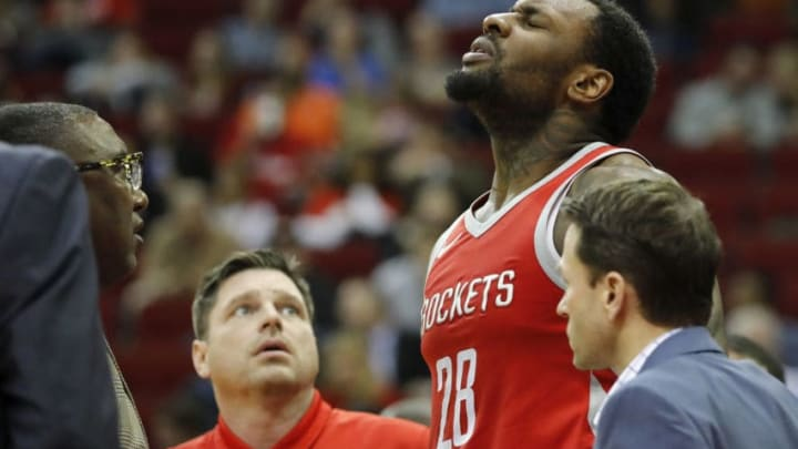 HOUSTON, TX - JANUARY 10: Members of the Houston Rockets training staff tend to Tarik Black