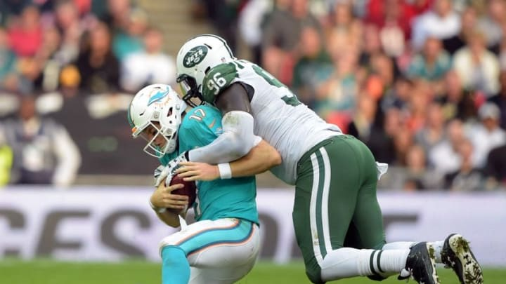 Oct 4, 2015; London, United Kingdom; New York Jets defensive end Muhammad Wilkerson (96) sacks Miami Dolphins quarterback Ryan Tannehill (17) in Game 12 of the NFL International Series at Wembley Stadium.The Jets defeated the Dolphins 27-14. Mandatory Credit: Kirby Lee-USA TODAY Sports