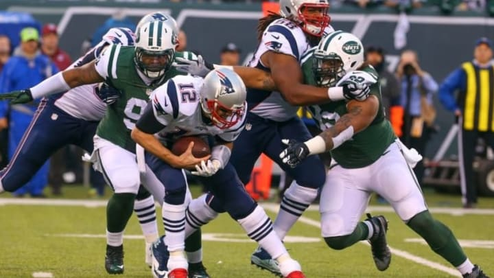 Dec 27, 2015; East Rutherford, NJ, USA; New England Patriots quarterback Tom Brady (12) is sacked by New York Jets defensive end Sheldon Richardson (91) during the second half at MetLife Stadium. The Jets defeated the Patriots 26-20 in overtime. Mandatory Credit: Ed Mulholland-USA TODAY Sports