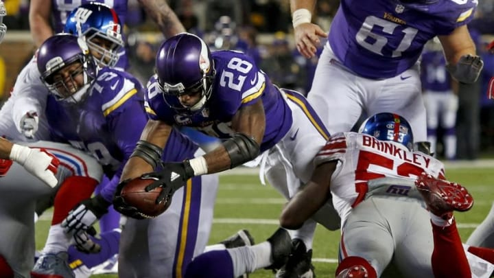 Dec 27, 2015; Minneapolis, MN, USA; Minnesota Vikings running back Adrian Peterson (28) reaches across the goal line for a touchdown against the New York Giants in the third quarter at TCF Bank Stadium. The Vikings win 49-17. Mandatory Credit: Bruce Kluckhohn-USA TODAY Sports