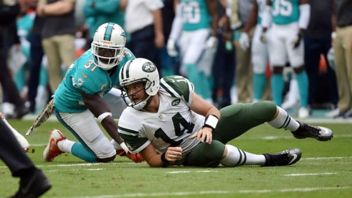 Nov 6, 2016; Miami Gardens, FL, USA; New York Jets quarterback Ryan Fitzpatrick (14) is tackled by Miami Dolphins safety Michael Thomas (31) during the first half at Hard Rock Stadium. Mandatory Credit: Steve Mitchell-USA TODAY Sports