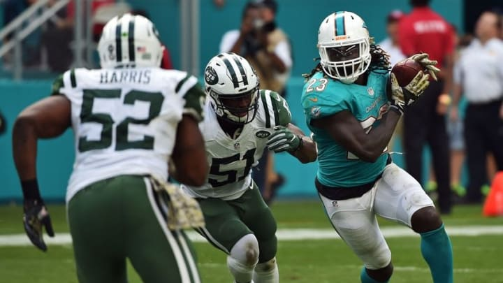 Nov 6, 2016; Miami Gardens, FL, USA; Miami Dolphins running back Jay Ajayi (23) carries the ball as New York Jets linebacker Julian Stanford (51) and New York Jets linebacker David Harris (52) both make the tackle during the first half at Hard Rock Stadium. Mandatory Credit: Steve Mitchell-USA TODAY Sports