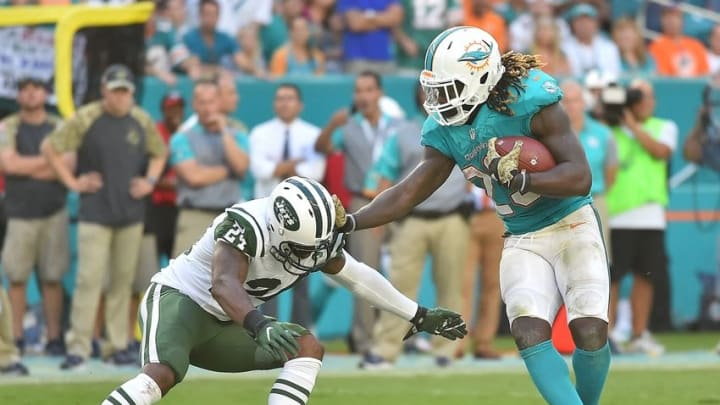 Nov 6, 2016; Miami Gardens, FL, USA; Miami Dolphins running back Jay Ajayi (23) pushes off of New York Jets cornerback Darrelle Revis (24) during the second half at Hard Rock Stadium. The Miami Dolphins defeat the New York Jets 27-23. Mandatory Credit: Jasen Vinlove-USA TODAY Sports