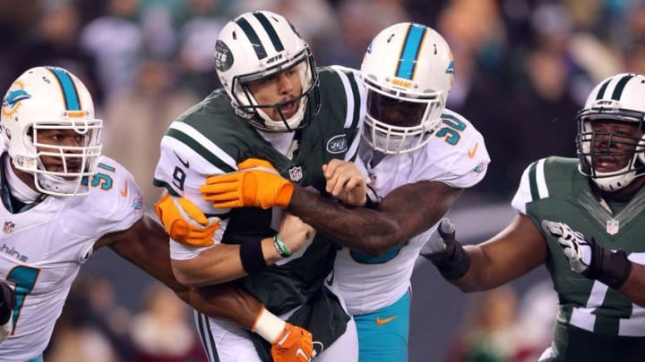 Dec 17, 2016; East Rutherford, NJ, USA; New York Jets quarterback Bryce Petty (9) is hit after throwing a pass by Miami Dolphins defensive end Andre Branch (50) during the first quarter at MetLife Stadium. Mandatory Credit: Brad Penner-USA TODAY Sports
