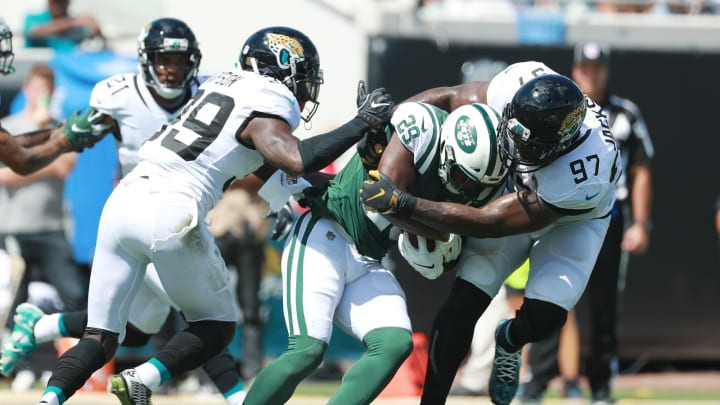JACKSONVILLE, FL – SEPTEMBER 30: Bilal Powell #29 of the New York Jets is tackled by Tashaun Gipson #39 and Malik Jackson #97 of the Jacksonville Jaguars during their game at TIAA Bank Field on September 30, 2018 in Jacksonville, Florida. (Photo by Scott Halleran/Getty Images)
