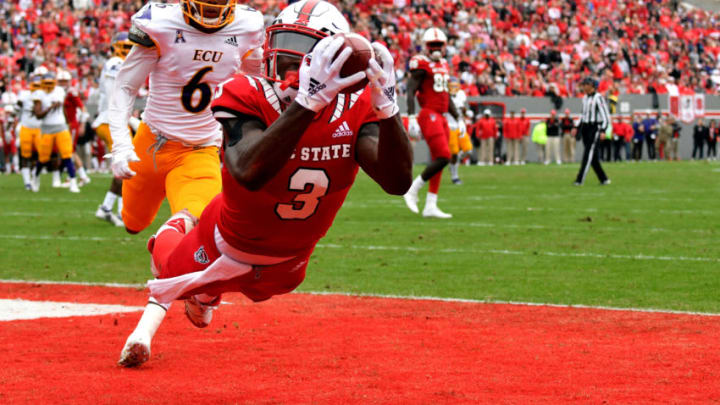 RALEIGH, NC - DECEMBER 01: Kelvin Harmon #3 of the North Carolina State Wolfpack catches a pass for a 14-yard touchdown against Marcus Holton Jr. #6 of the East Carolina Pirates in the first quarter at Carter-Finley Stadium on December 1, 2018 in Raleigh, North Carolina. (Photo by Lance King/Getty Images)