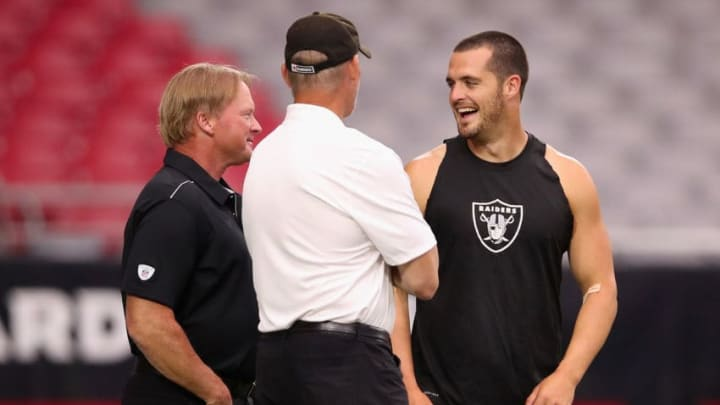 GLENDALE, ARIZONA - AUGUST 15: (L-R) Head coach Jon Gruden, general manager Mike Mayock and quarterback Derek Carr #4 of the Oakland Raiders talk on the field before the NFL preseason game against the Arizona Cardinals at State Farm Stadium on August 15, 2019 in Glendale, Arizona. (Photo by Christian Petersen/Getty Images)