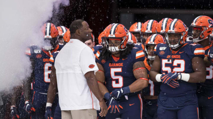 SYRACUSE, NY - SEPTEMBER 28: Syracuse Orange players and head coach Dino Babers stand amidst special effects before the game against the Holy Cross Crusaders at the Carrier Dome on September 28, 2019 in Syracuse, New York. (Photo by Brett Carlsen/Getty Images)