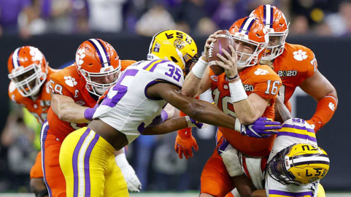 NEW ORLEANS, LOUISIANA - JANUARY 13: Trevor Lawrence #16 of the Clemson Tigers is sacked by K'Lavon Chaisson #18 of the LSU Tigers and Damone Clark #35 of the LSU Tigers in the College Football Playoff National Championship game at Mercedes Benz Superdome on January 13, 2020 in New Orleans, Louisiana. (Photo by Kevin C. Cox/Getty Images)