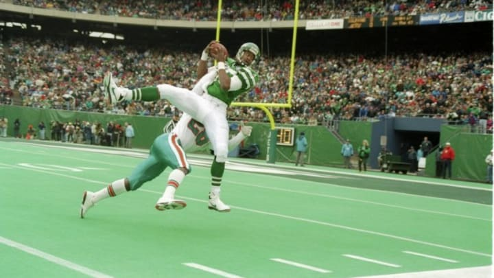 30 Nov 1994: Wide receiver Rob Moore of the New York Jets catches the ball as Miami Dolphins defensive back Gene Atkins tackles him during a game at Giants Stadium in East Rutherford, New Jersey. The Dolphins won the game, 28-24. Mandatory Credit: Simon