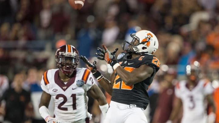 ORLANDO, FL - DECEMBER 28: Wide receiver James Washington #28 of the Oklahoma State Cowboys looks to catch a pass in front of safety Reggie Floyd #21 of the Virginia Tech Hokies on December 28, 2017 at Camping World Stadium in Orlando, Florida. (Photo by Michael Chang/Getty Images)