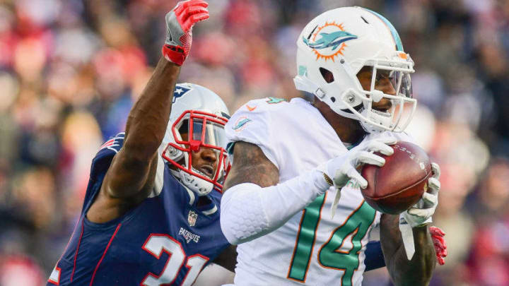 FOXBORO, MA - NOVEMBER 26: Jarvis Landry #14 of the Miami Dolphins carries the ball as he is tackled by Jonathan Jones #31 of the New England Patriots during the second quarter of a game at Gillette Stadium on November 26, 2017 in Foxboro, Massachusetts. (Photo by Adam Glanzman/Getty Images)
