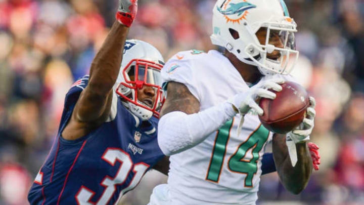 FOXBORO, MA – NOVEMBER 26: Jarvis Landry #14 of the Miami Dolphins carries the ball as he is tackled by Jonathan Jones #31 of the New England Patriots during the second quarter of a game at Gillette Stadium on November 26, 2017 in Foxboro, Massachusetts. (Photo by Adam Glanzman/Getty Images)