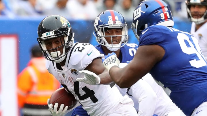 EAST RUTHERFORD, NJ – SEPTEMBER 09: T.J. Yeldon #24 of the Jacksonville Jaguars runs with the ball against Eli Apple #24 and Dalvin Tomlinson #94 of the New York Giants in the second half at MetLife Stadium on September 9, 2018 in East Rutherford, New Jersey. (Photo by Mike Lawrie/Getty Images)