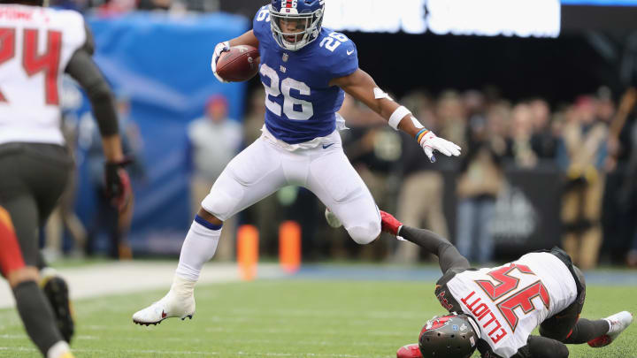 EAST RUTHERFORD, NJ – NOVEMBER 18: Running back Saquon Barkley #26 of the New York Giants carries the ball as he jumps over cornerback Javien Elliott #35 of the Tampa Bay Buccaneers for a 4-yard gain during the second quarter at MetLife Stadium on November 18, 2018 in East Rutherford, New Jersey. (Photo by Elsa/Getty Images)