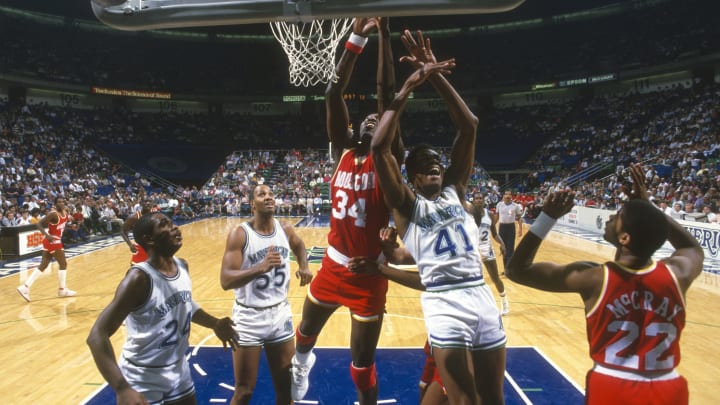 DALLAS, TX – CIRCA 1990: Hakeem Olajuwon #34 of the Houston Rockets battles for a rebound with Sam Perkins #41 of the Dallas Mavericks during an NBA basketball game circa 1990 at Reunion Arena in Dallas, Texas. Olajuwon played for the Rockets from 1984-2002. (Photo by Focus on Sport/Getty Images)