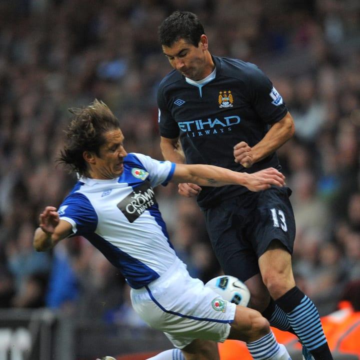 Salgado thunders into a challenge with Manchester City's Aleksandar Kolarov