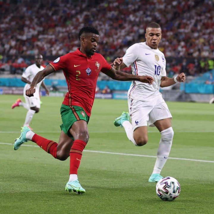 Nelson Semedo runs alongside Kylian Mbappe