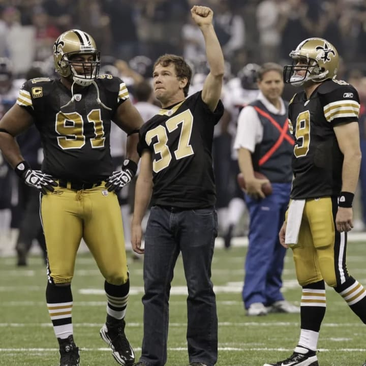 Former New Orleans Saints football player Steve Gleason raises his hand to the crowd before the first half of an NFL football game against the Houston