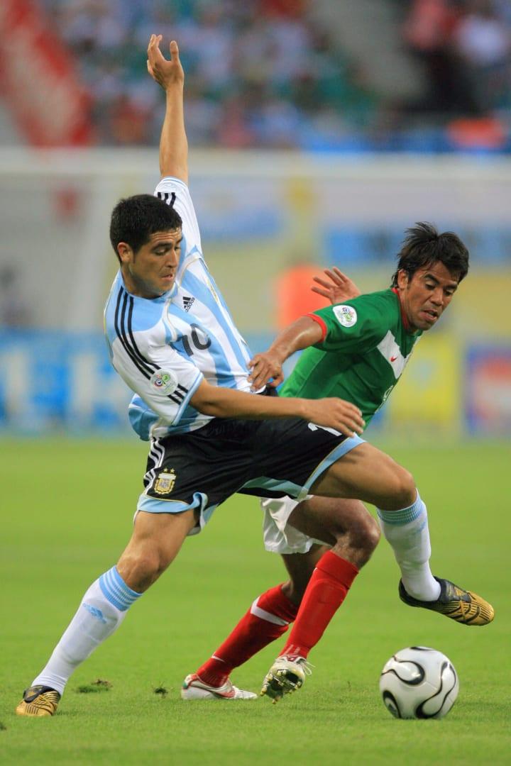 Juan Román Riquelme disputando el balón junto a Pável Pardo.