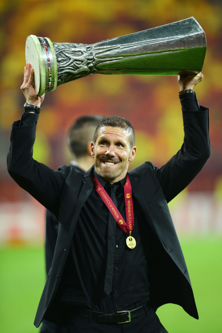 Simeone hoists aloft the first of two Europa League trophies he would win as manager of Atletico Madrid