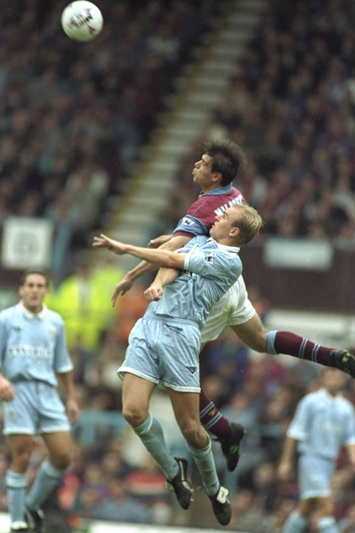 Savo Milosevic of Aston Villa and David Busst of Coventry City