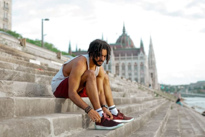 man in exercise clothes tying shoe