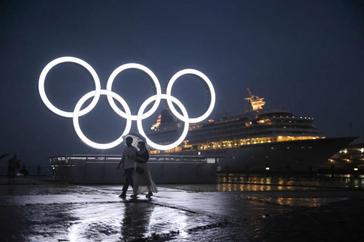 A couple with an umbrella walks past the illuminated Olympic...