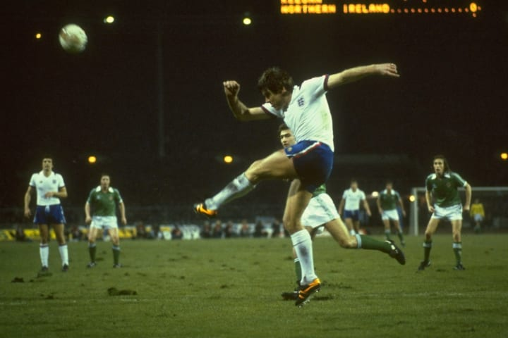 Emlyn Hughes of England clears the ball as Martin O''Neil of Northern Ireland looks on