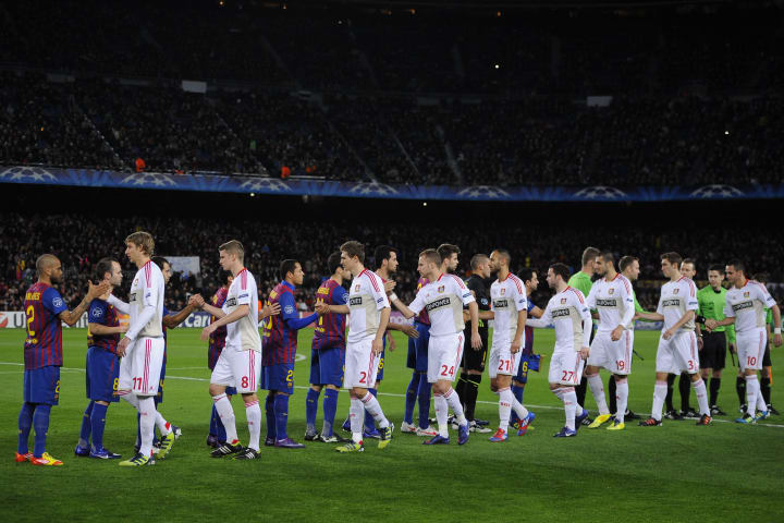 The FC Barcelona and Bayer 04 Leverkusen players shake hands ahead of the Champions League round of 16 second leg