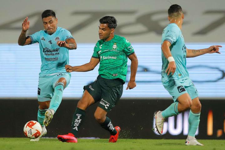Jugadores de Mazatlán pelean un balón ante un jugador de Santos Laguna.