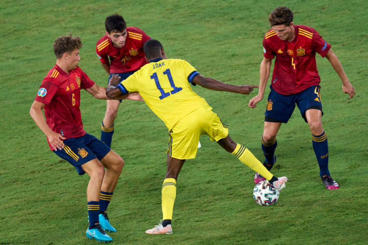 Alexander Isak is marshalled by three Spain players