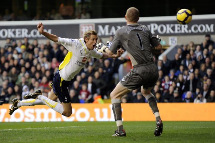 Tottenham Hotspurs' Peter Crouch (L) hea
