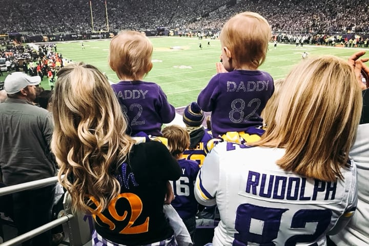 Kyle Rudolph's wife and two daughters watch a Minnesota Vikings game from the stands.