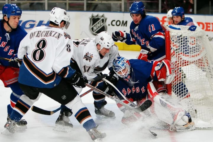UNITED STATES - MARCH 16: New York Rangers' goalie Henrik Lundqvist is hit by the Washington Capitals' Chris Clark as Clark scores in the second perio