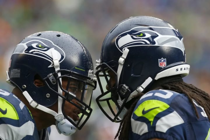 Seattle Seahawks linebacker Bobby Wagner (54) and cornerback Richard Sherman (25) motivate each other on the sideline during an NFL Championship Playo