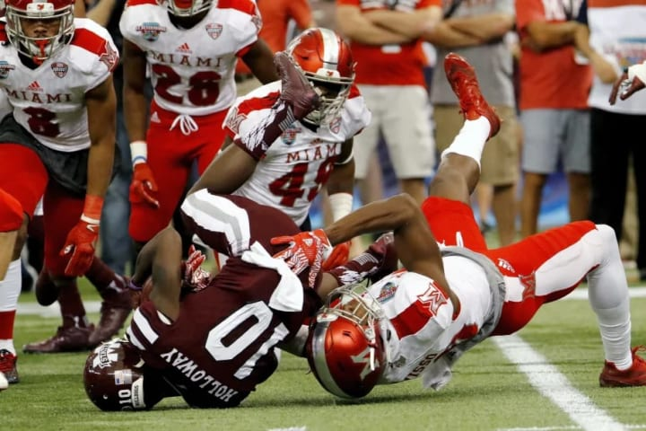 ST. PETERSBURG, FL - DECEMBER 26: Running back Brandon Holloway #10 of the Mississippi State Bulldogs is tackled by wide receiver Sam Shisso #10 of th