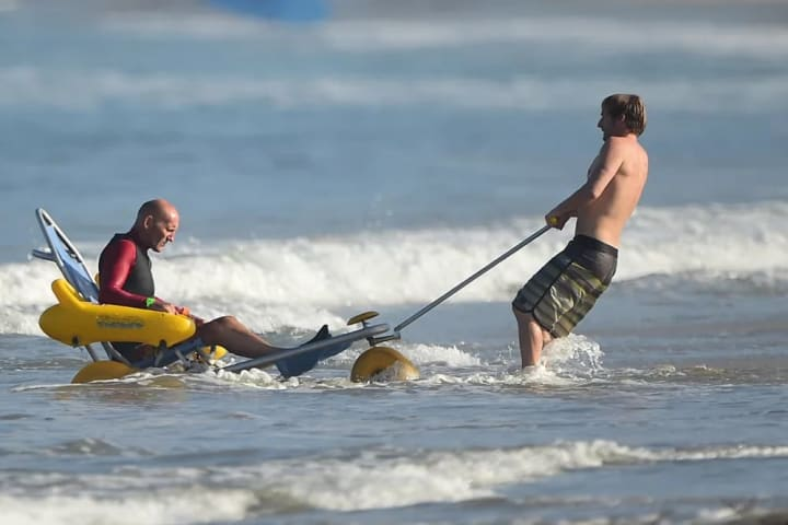 Spike Kane gets a bit of help after a surf.