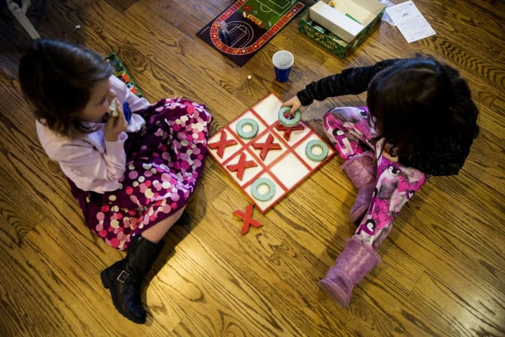 Abigail (left) and Julia play tic-tac-toe during the breakfast.