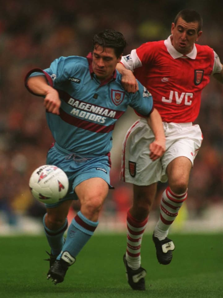 Tony Cottee (left) and Nigel Winterburn (right) battle for the ball.