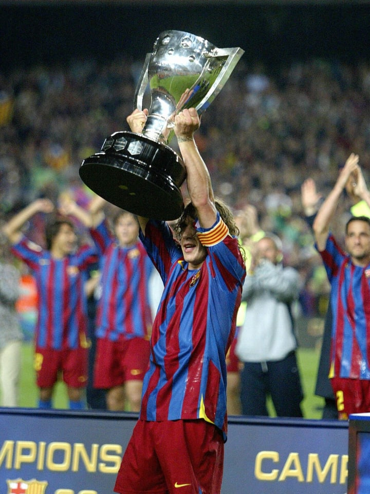 Barcelona captain Carles Puyol holds up