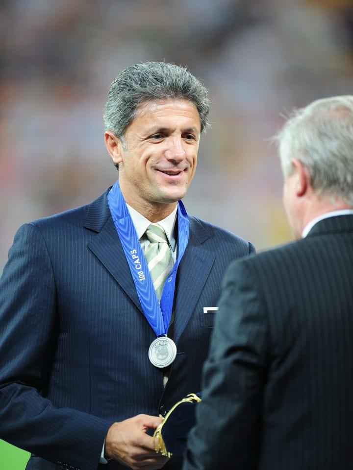 Gheorge  Popescu (L) receives a cap from