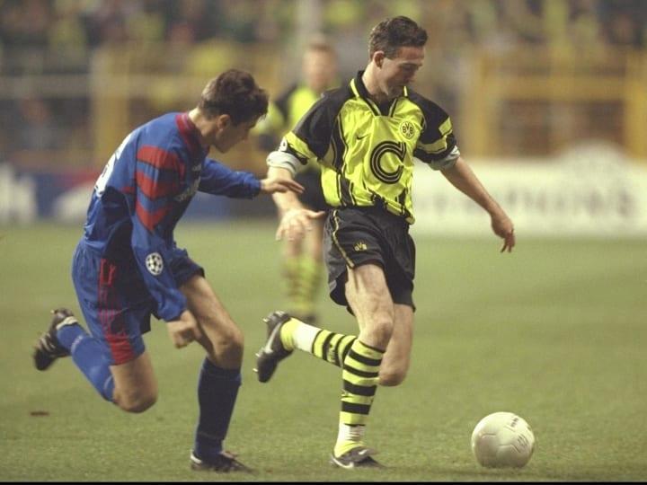 Ilie Iulian Miu of Steau (left) pursues Paul Lambert of Dortmund