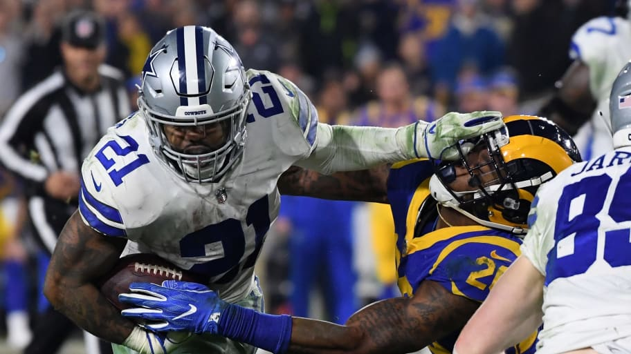 LOS ANGELES, CA - JANUARY 12:  Ezekiel Elliott #21 of the Dallas Cowboys stiff arms Mark Barron #26 of the Los Angeles Rams in the fourth quarter in the NFC Divisional Playoff game at Los Angeles Memorial Coliseum on January 12, 2019 in Los Angeles, California.  (Photo by Harry How/Getty Images)